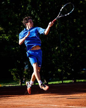 Tennista in volo mentre colpisce la palla, campo da tennis del Centro Le Sequoie